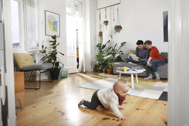 Parents sitting on couch, using laptop, while daughter is playing on the floor - FKF02918