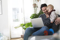 father sitting on couch with his little daughter, using laptop - FKF02924