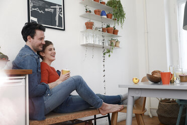 Happy couple sitting in kitchen, leaning against each other - FKF02933