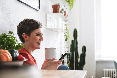 Woman sitting in kitchen, drinking coffee and checking smartphone messages - FKF02936