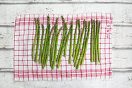 Organic green asparagus on red-white kitchen towel - LVF06971