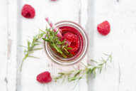 Glass bottle of homemade raspberry lemonade flavoured with rosemary - LVF06974