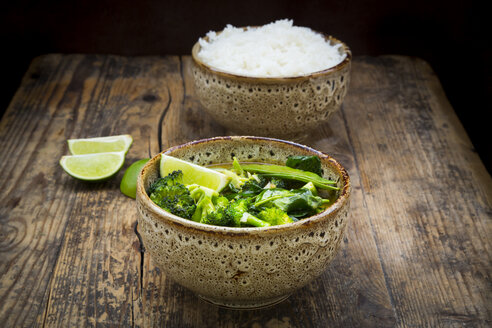 Green thai curry with broccoli, pak choi, snow peas, baby spinach, lime and bowl of rice in the background - LVF06979