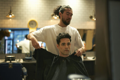 Barber putting gown onto male customer in barber shop - CUF06483