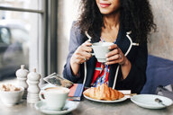 Cropped shot of woman holding coffee cup in cafe - CUF06486