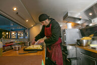 Chef preparing pizza in food stall van at night - CUF06513