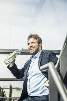 Businessman drinking bottled water on office stairway - CUF06519