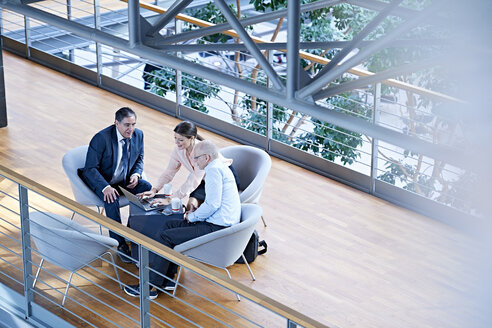 High angle view of businessmen and businesswoman meeting on office balcony - CUF06552
