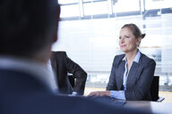 Over shoulder view of businesswoman and men in office meeting - CUF06561