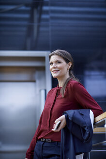 Businesswoman leaning on office handrail holding smartphone - CUF06564