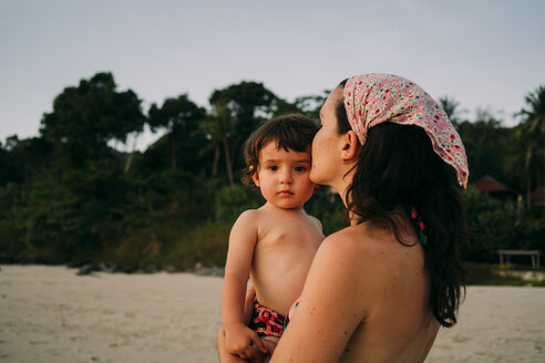 Mother holding and kissing her little daughter on the beach by sunset - GEMF01980
