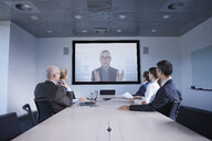 Businessmen and women watching office conference call - CUF06612