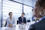 Over shoulder view of businesswomen and men listening at office meeting - CUF06615