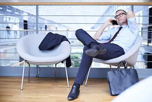 Businessman sitting making smartphone call on office balcony - CUF06624