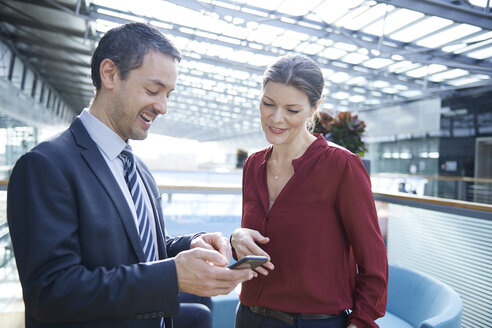 Businessman and woman looking at smartphone in office atrium - CUF06630