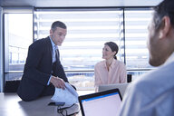 Businessmen and woman meeting at office desk - CUF06657