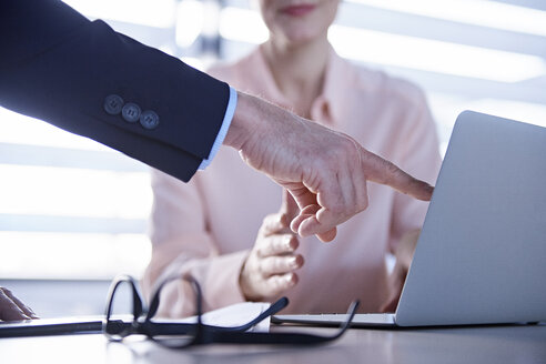 Cropped shot of businessman pointing at laptop on office desk - CUF06660