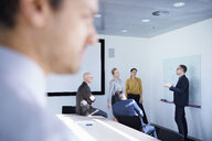 Businessman making whiteboard presentation in conference room meeting - CUF06696