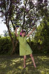 Singing girl with headphones and smartphone dancing in the garden - LVF06982