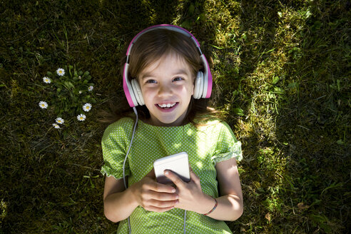 Portrait of little girl lying on meadow listening music with headphones and smartphone - LVF06985