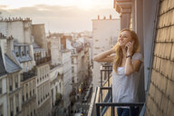 France, Paris, portrait of smiling woman on the phone standing on balcony in the evening - JUNF01046