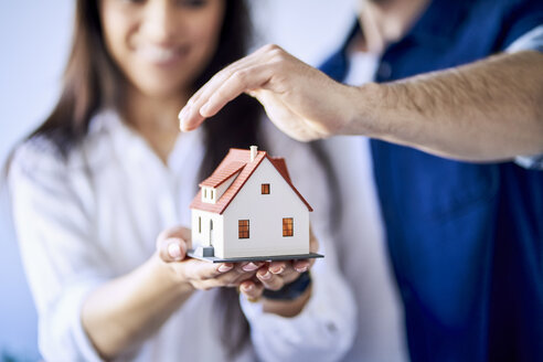 Close-up of couple holding model of new home - BSZF00388