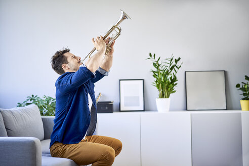 Man sitting on couch playing trumpet - BSZF00391