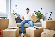 Frustrated man sitting on couch surrounded by cardboard boxes - BSZF00397