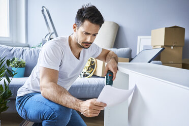 Man reading instructions while assembling furniture in new apartment - BSZF00409