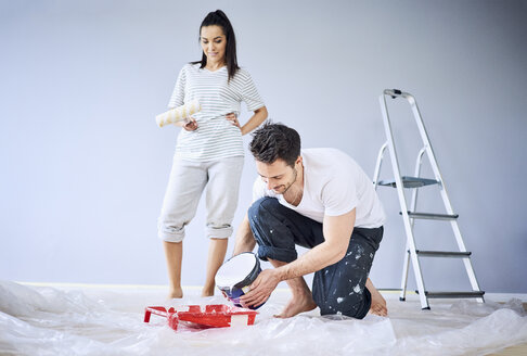 Happy couple painting in apartment together - BSZF00415