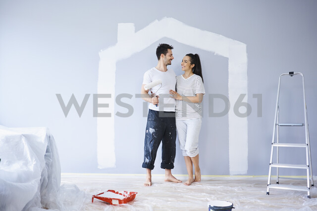 Happy couple painting in new apartment with house shape on wall - BSZF00421 - Bartek Szewczyk/Westend61