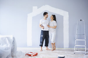 Happy couple painting in new apartment with house shape on wall - BSZF00421