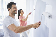 Happy couple painting wall in apartment together - BSZF00427