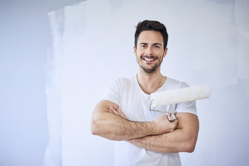 Portrait of smiling man painting wall in apartment - BSZF00430