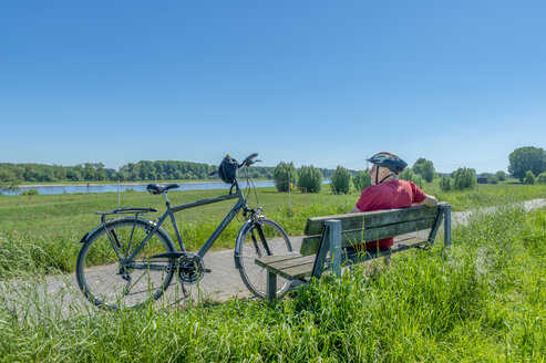 Germany, Zons, senior man with bicycle resting on a bench looking at view - FRF00658