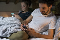 Young couple sitting up in bed looking at smartphones - CUF06837