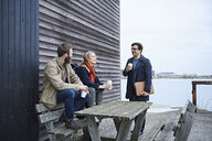 Male and female designers sitting on bench at meeting outside design studio - CUF06873