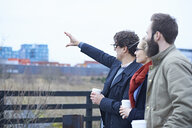 Rear view of design team pointing outside design studio - CUF06876