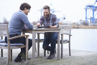 Two male designers having meeting on waterfront outside design studio - CUF06918
