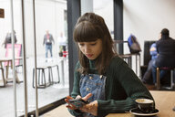 Young woman in cafe using smartphone touchscreen - CUF06945