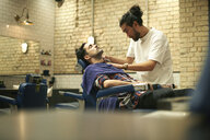 Hairdresser in barbershop giving customer wet shave - CUF06978