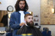 Hairdresser in barbershop putting protective cape on customer - CUF06981