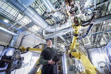 Apprentice engineer adjusting robot in car factory - CUF07026