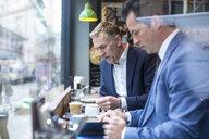 Two businessmen having working lunch in restaurant - CUF07047