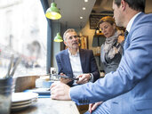 Businessmen and woman having discussion in restaurant window seat - CUF07050