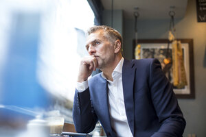 Mature businessman looking out of restaurant window - CUF07053