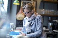 Mature businesswoman doing paperwork in restaurant - CUF07056