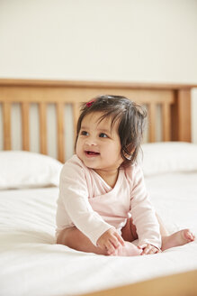 Happy baby girl sitting up on bed playing with her feet - CUF07107