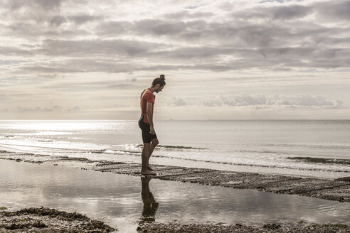 Man on shoreline looking away at view of sea - CUF07149