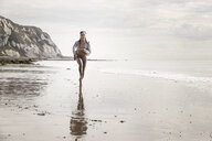 Front view of young female runner running barefoot along beach - CUF07155